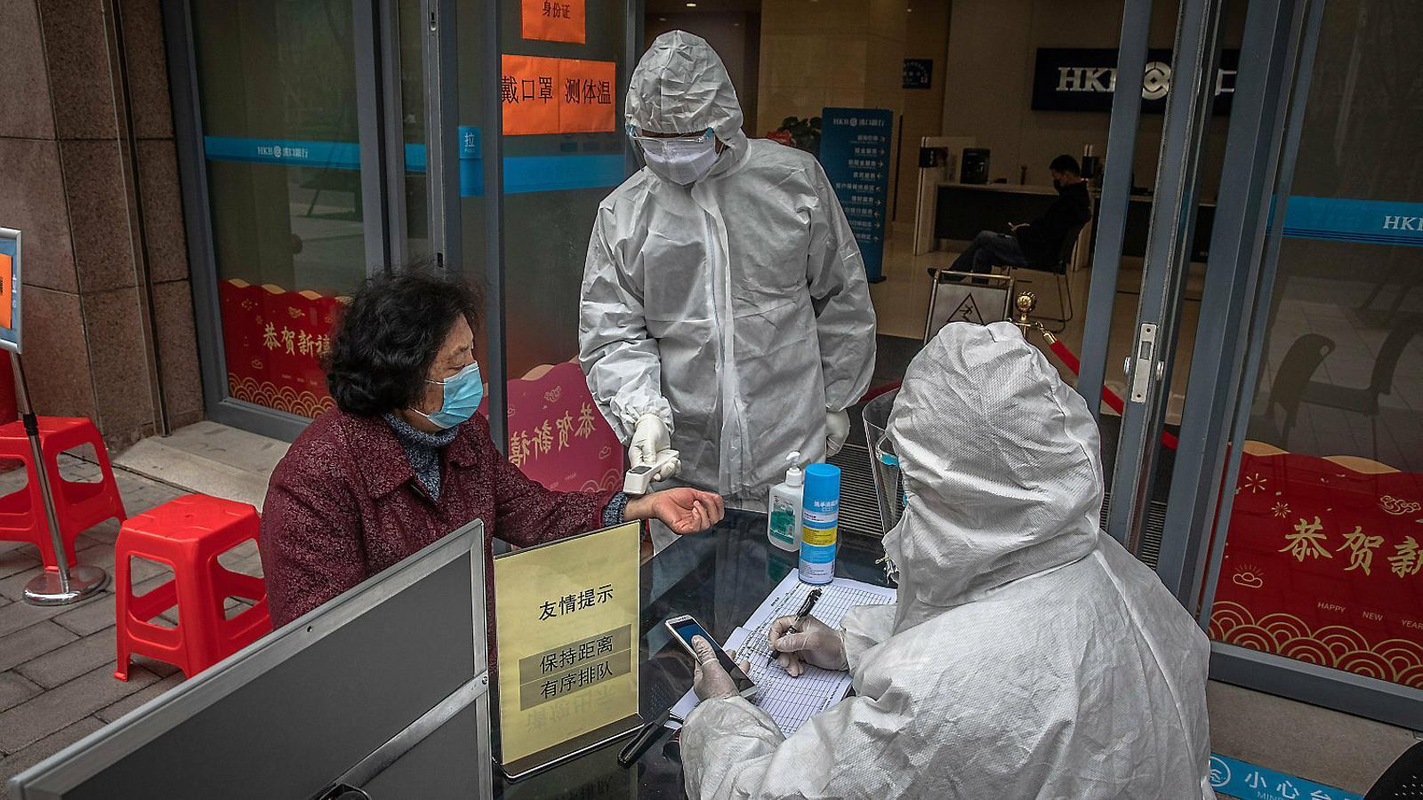 Un operari prenent la temperatura a una dona mentre el seu company recull informació del mòbil de la senyora, en una imatge d'ahir en una oficina bancària de Wuhan.