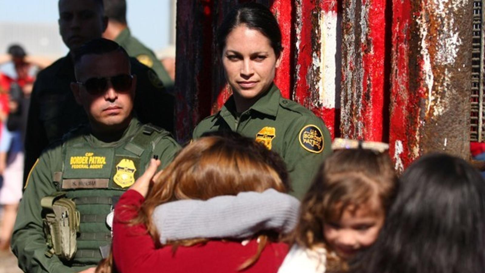 Dos guàrdies dels Estats Units miren l'abraçada de dos familiars separats per la frontera, a Tijuana.