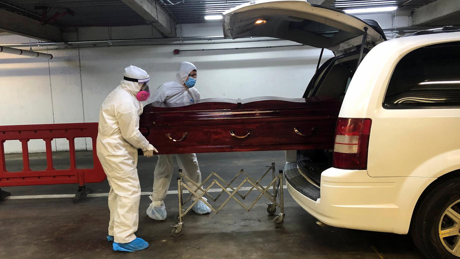 Dos treballadors dels serveis funeraris de Santiago de Xile traslladant el taüt d'una víctima del covid-19.