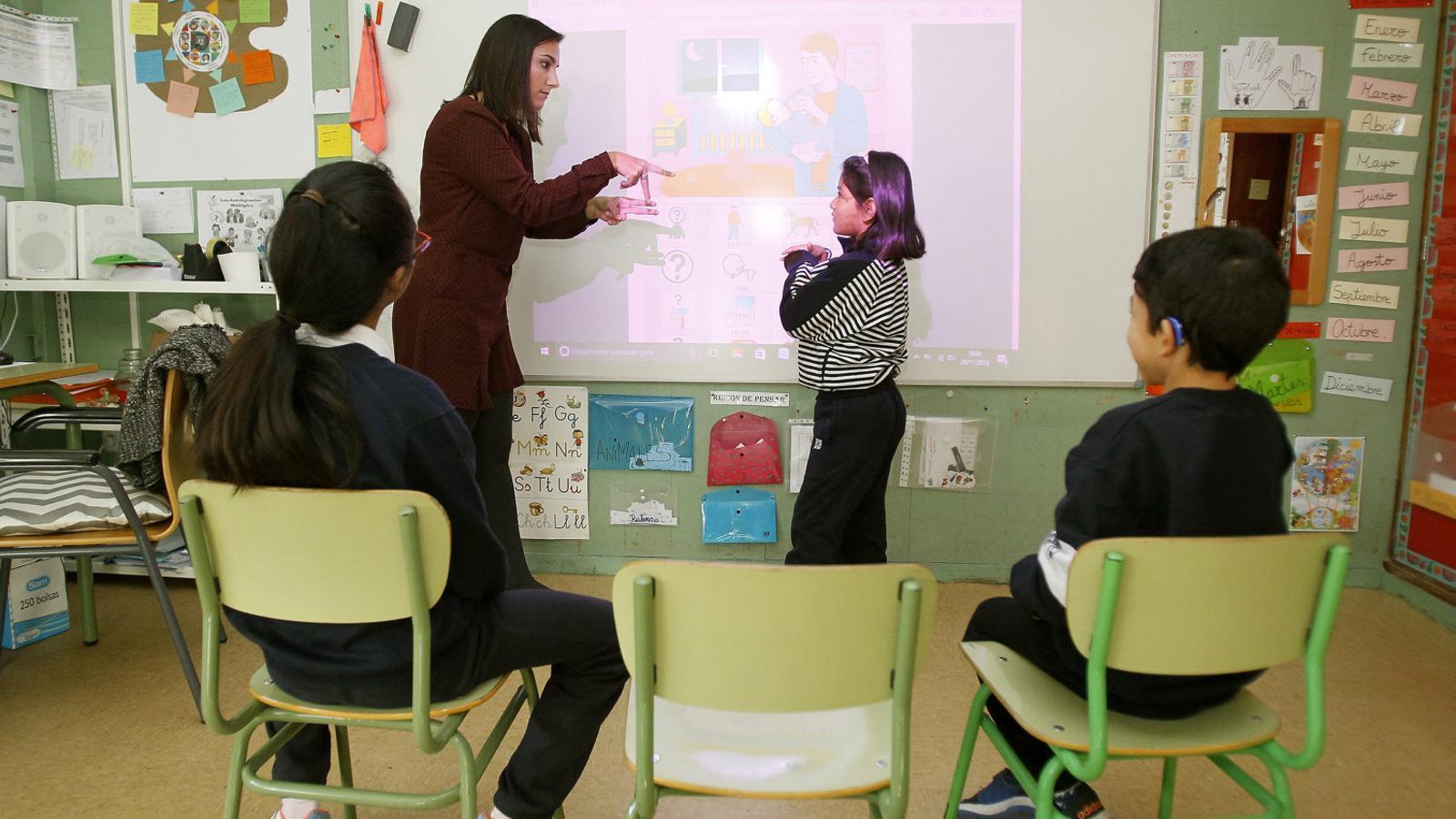Alumnes de Primària del col·legi La Puríssima, a Palma, escolten les explicacions de la professora en el temps de classe.