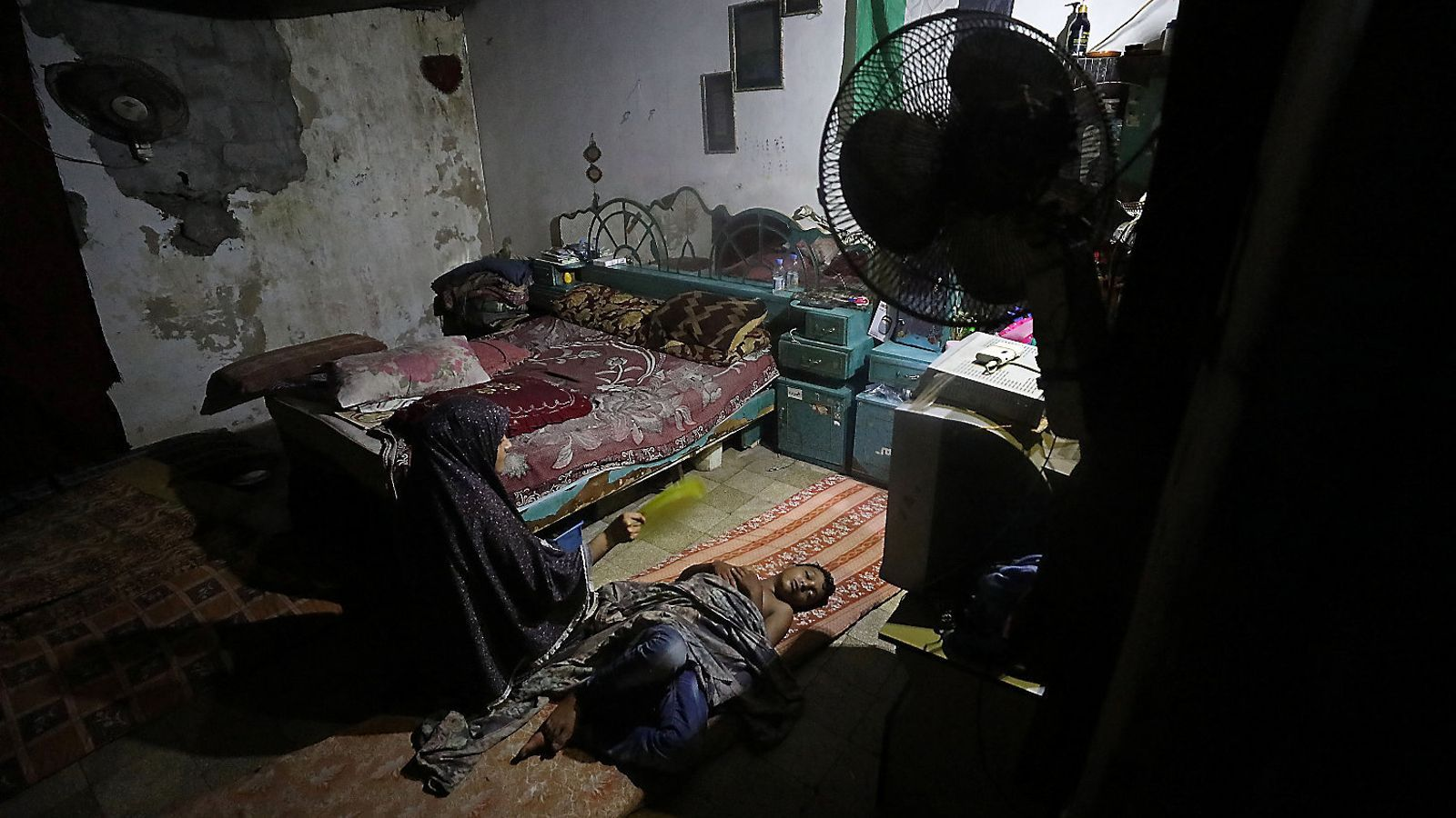 Una dona venta el seu fill dins la casa il·luminada amb bateries  al camp de refugiats de Jabàlia, al nord de Gaza.