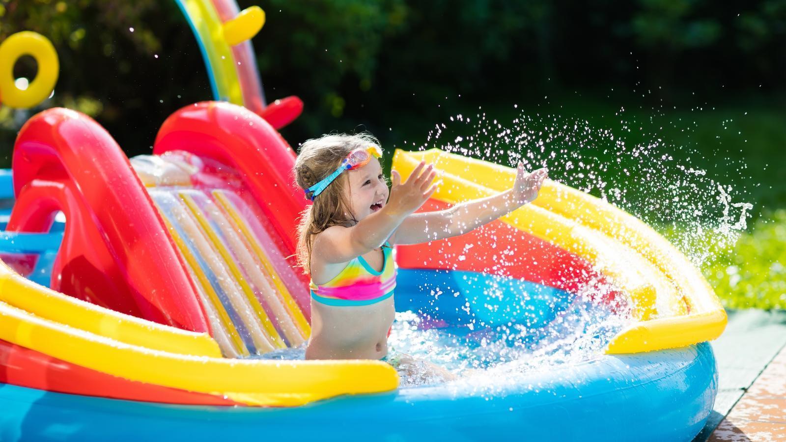 Una nena juga a una piscina inflable amb un tobogan dins