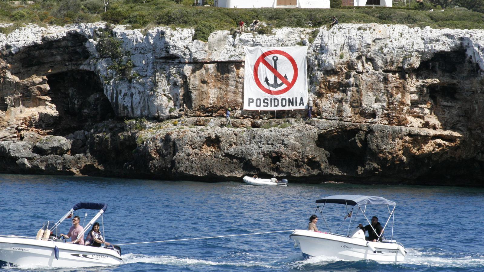 Moments en què Salvem Portocolom penja el cartell sobre la prohibició d'ancorar a la posidònia.