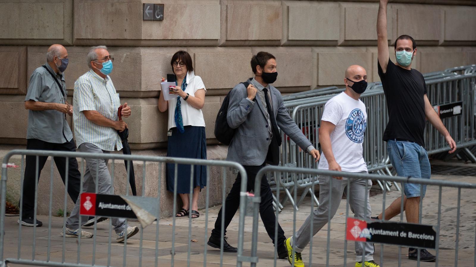 Els quatre acusats amb el seu advocat -al centre- a l'entrada de l'Audiència de Barcelona aquest dilluns