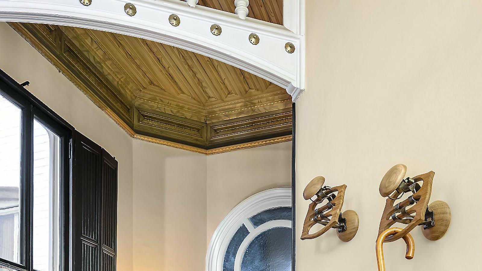 Una cadira dissenyada per Gaudí sota els penjadors que reprodueix BD.