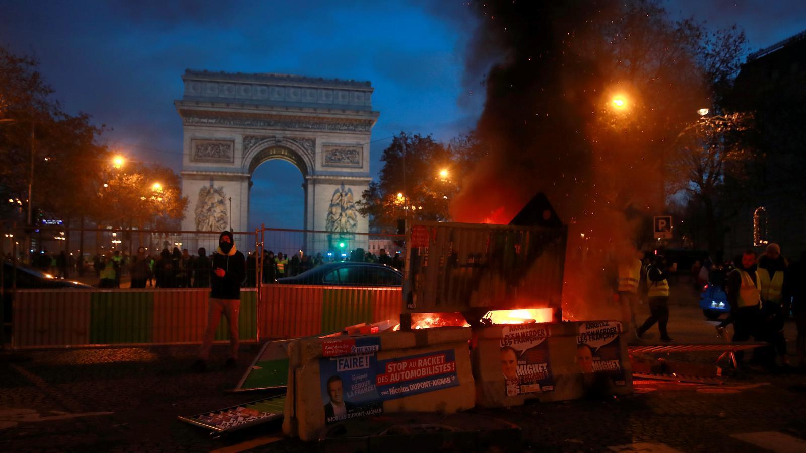 Un encaputxat observa al seu voltant darrere d'una barricada plantada al costat de l'Arc del Triomf, a París