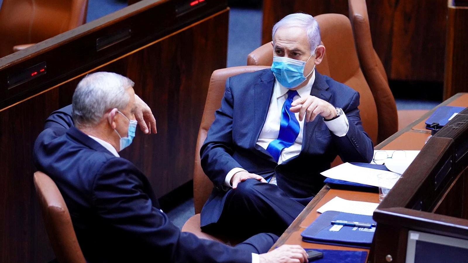 El primer ministre israelià, Benjamin Netanyahu, i Benny Gantz, porten màscares quan parlant a la cerimònia de jurament del nou govern, al parlament d'Israel, a Jerusalem.