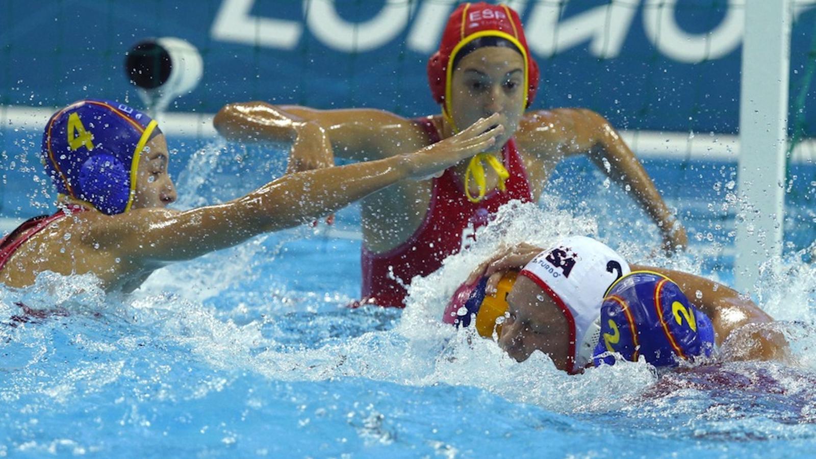 Marta Pascual (a la dreta) i Roser Tarragó lluiten amb la nord-americana Petri Heather durant la final de waterpolo