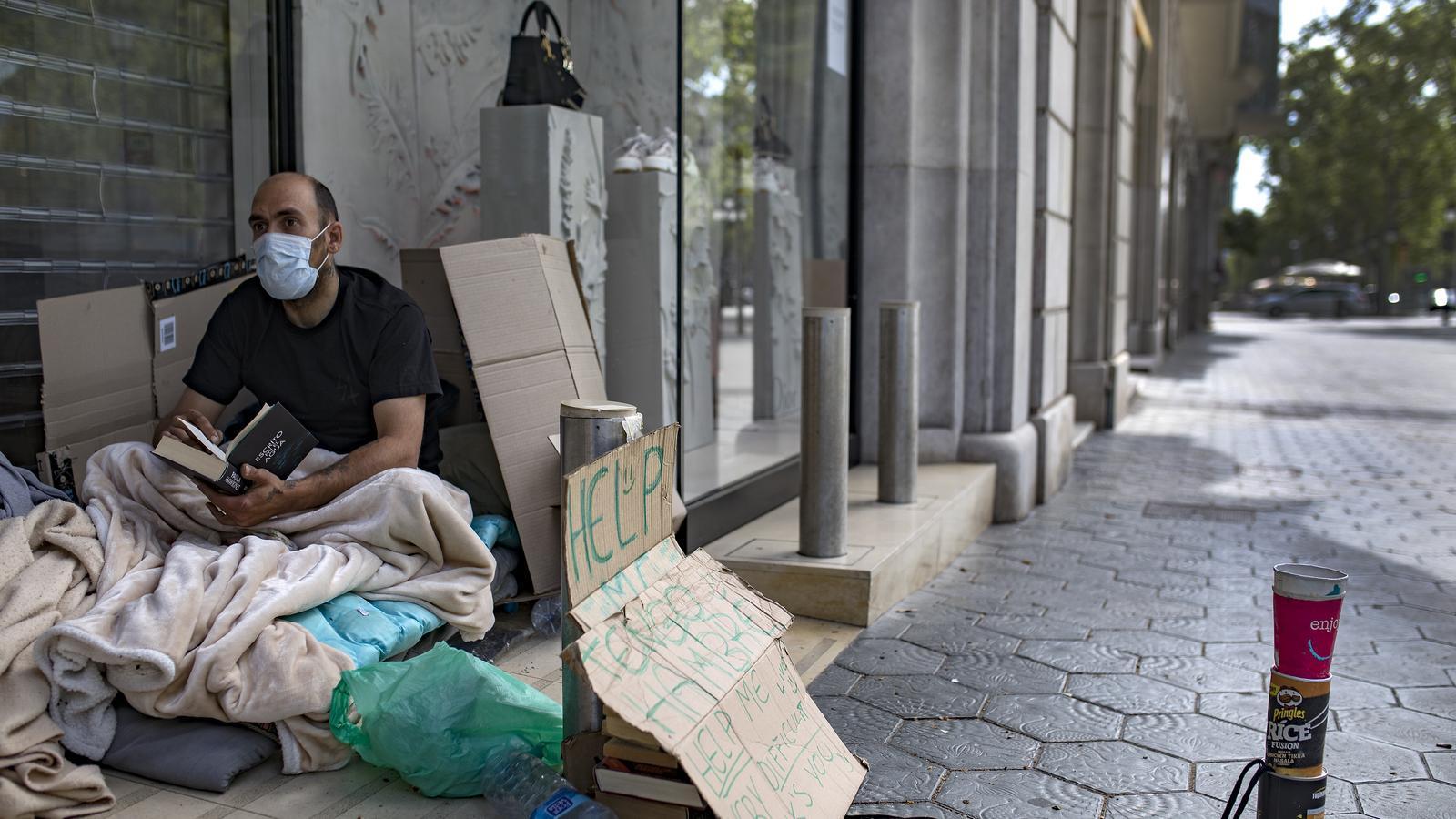 Un sense llar amb mascareta, aquest dimecres al passeig de Gràcia de Barcelona