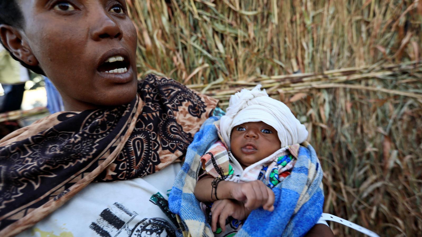Un nadó i una dona mentre fugen de la regió del Tigre i arriben al Sudan.