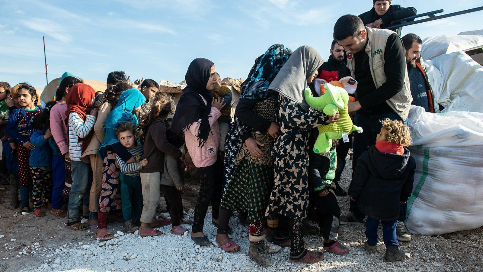 Nens i nenes desplaçats a Idlib fent cua per rebre ajuda humanitària.