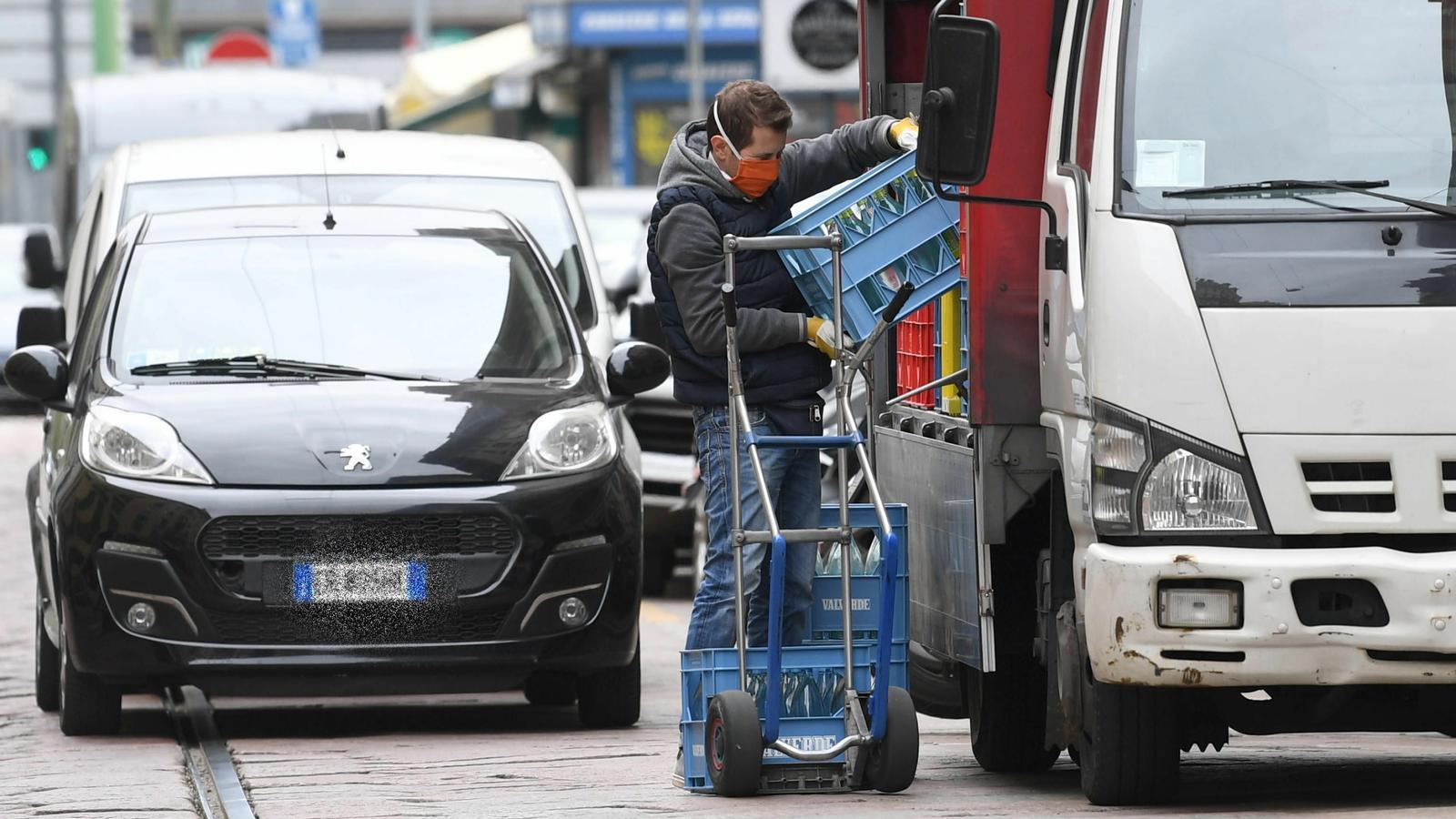 Un treballador amb mascareta descarrega ampolles d'un camió a Milà