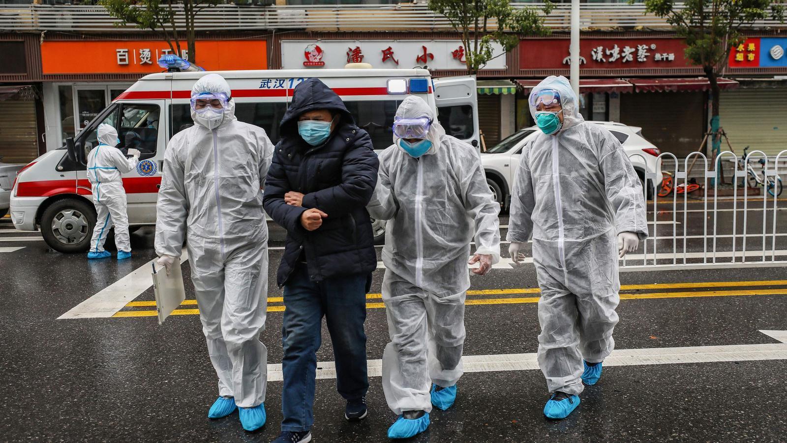 Membres del personal sanitari acompanyant un pacient  a un hospital de Wuhan