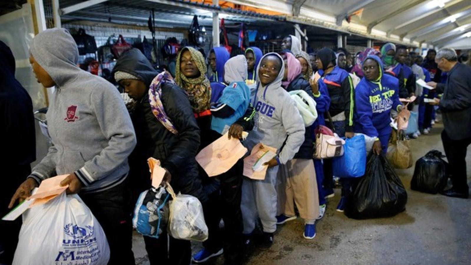 Desenes de subsaharians esperen embarcar a l'aeroport de Trípoli per tornar a casa, dins del programa de retorn voluntari impulsat per la UE.