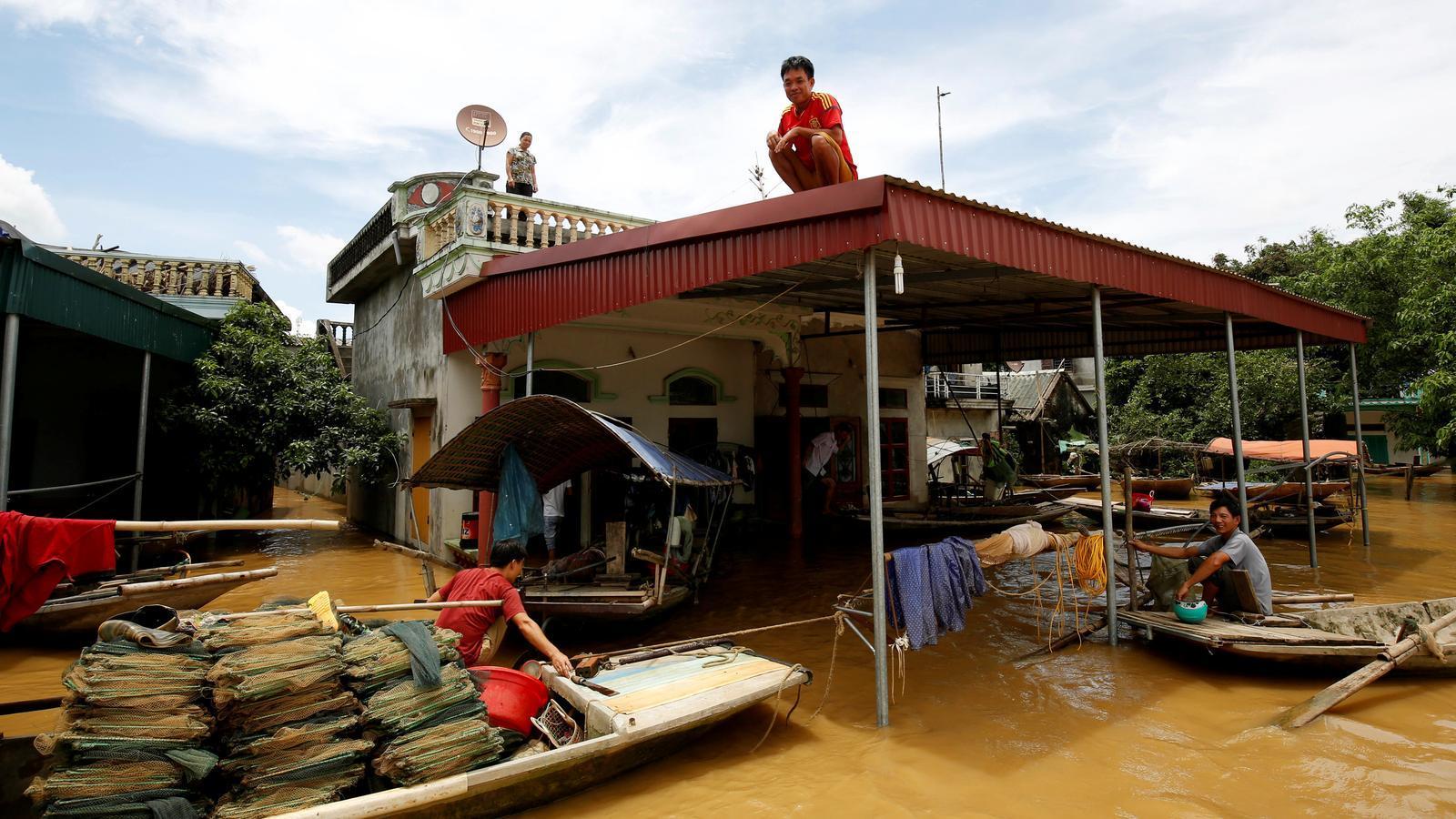 Un home esperant sobre de la teulada que el rescatin en les inundacions del nord del Vietnam