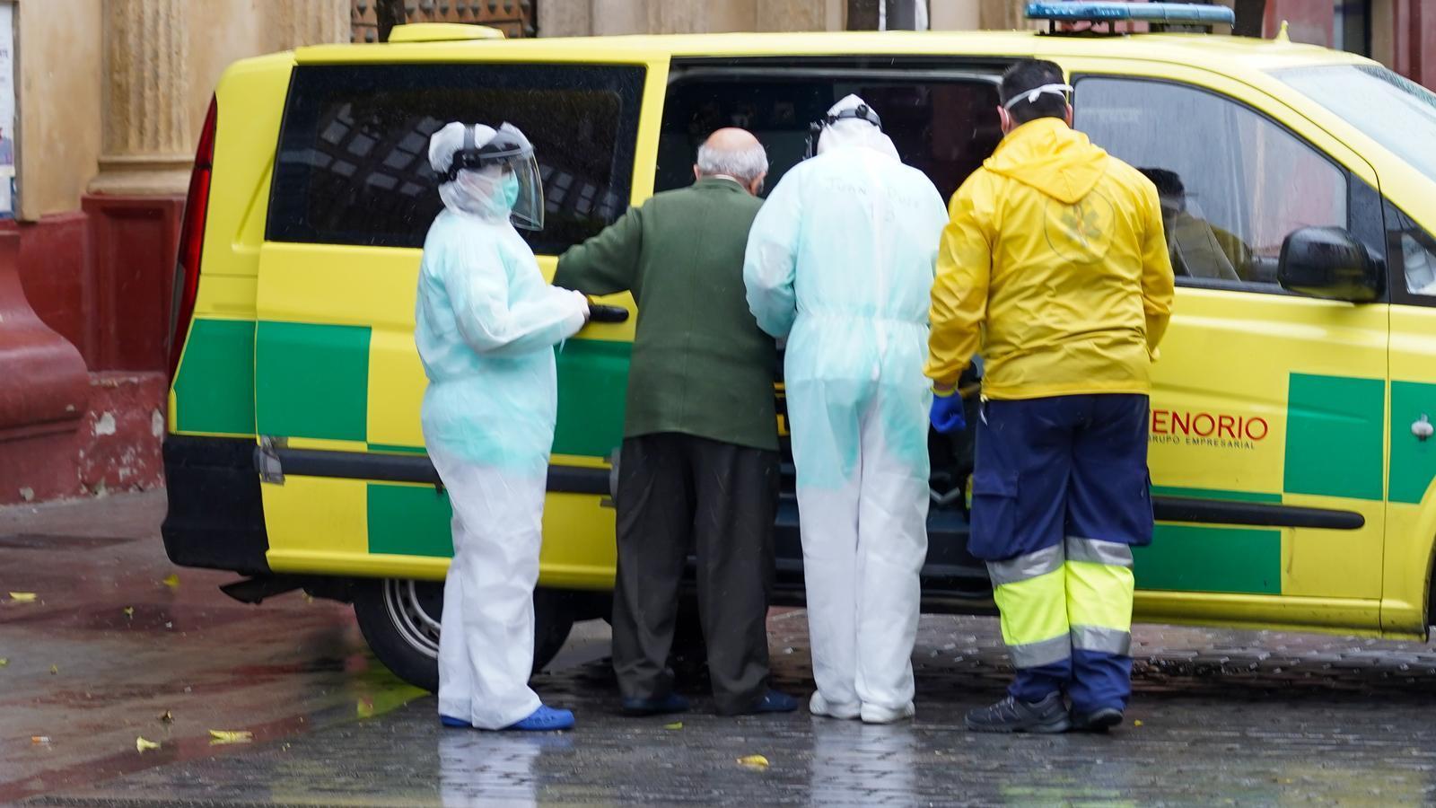 Sanitaris de la residència San Juan de Dios acompanyen un home gran cap a l'ambulància que el portarà a l'Hospital Virgen del Rocío de Sevilla