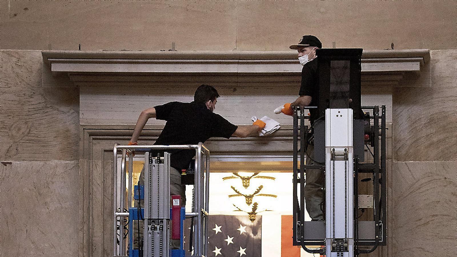 Personal de manteniment del Capitoli preparant les portes de la Sala Rotonda, dins del Capitoli, per a les cortines de la Inauguració de Joe Biden, el 20 de gener.