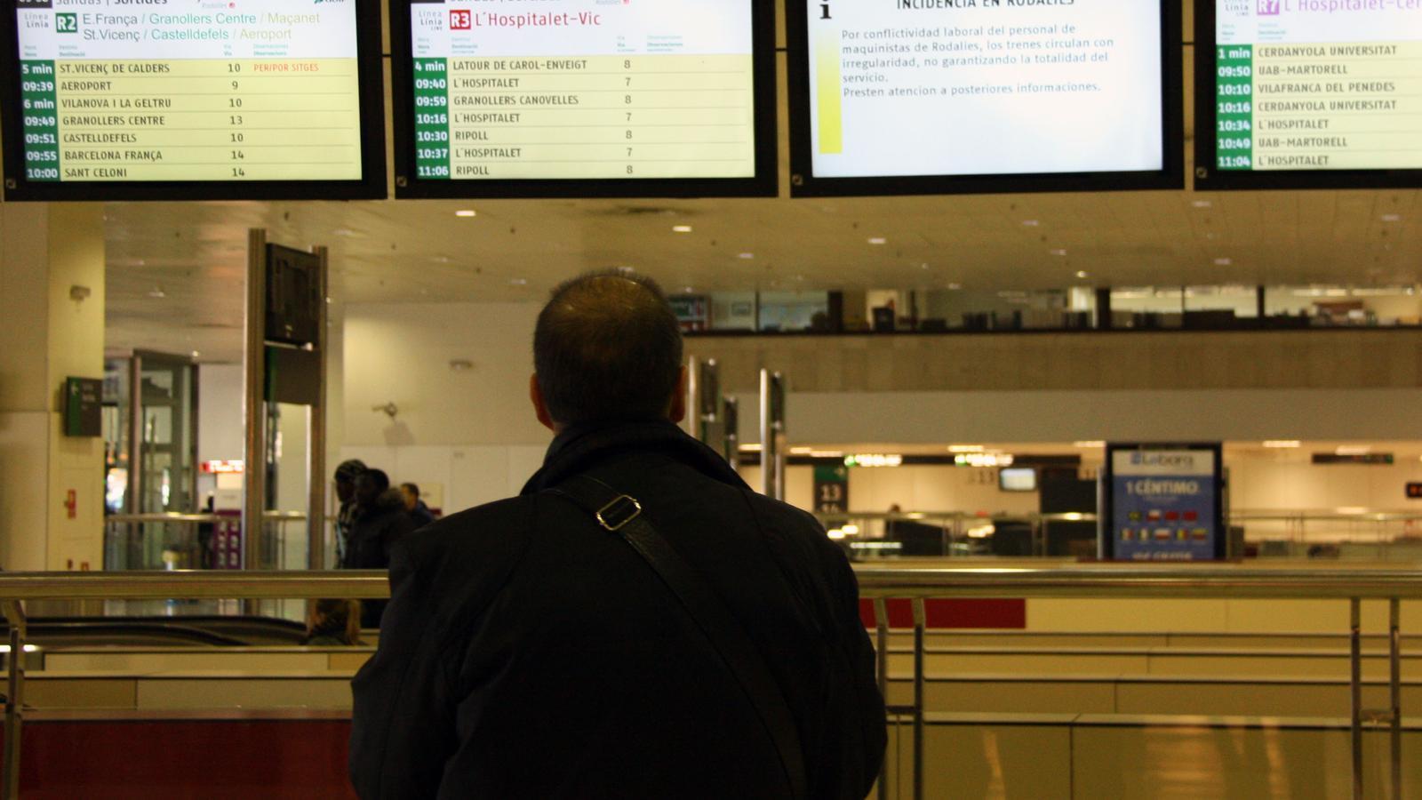 Un usuari observa el rètol que avisa de les incidències en el servei de Rodalies