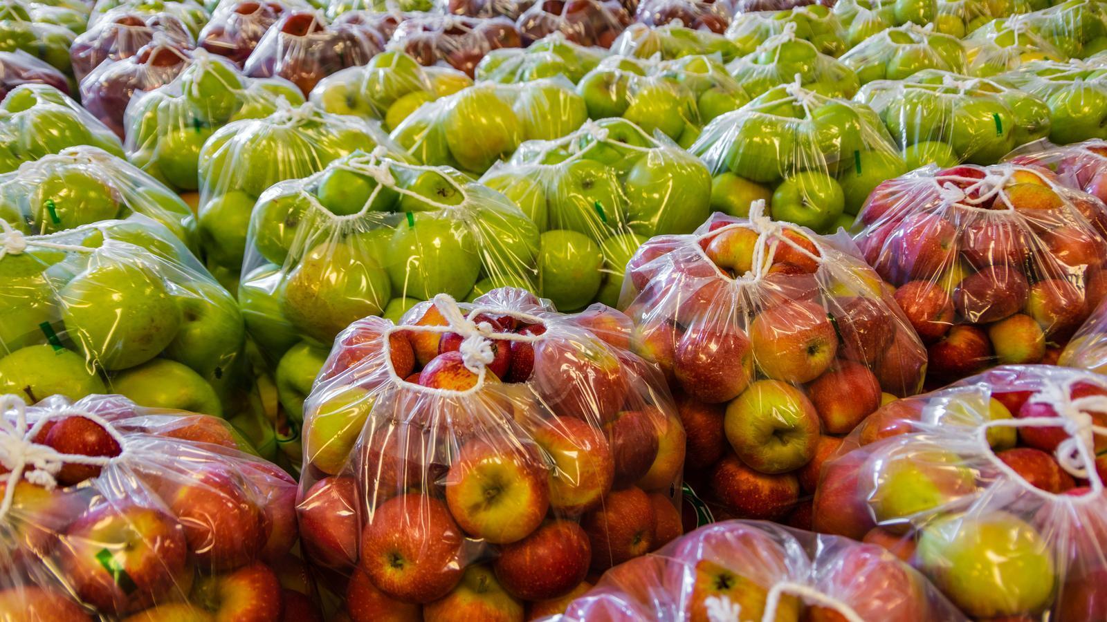 Milers de pomes embolicades en bosses de plàstic a punt per a la seva distribució / GETTY
