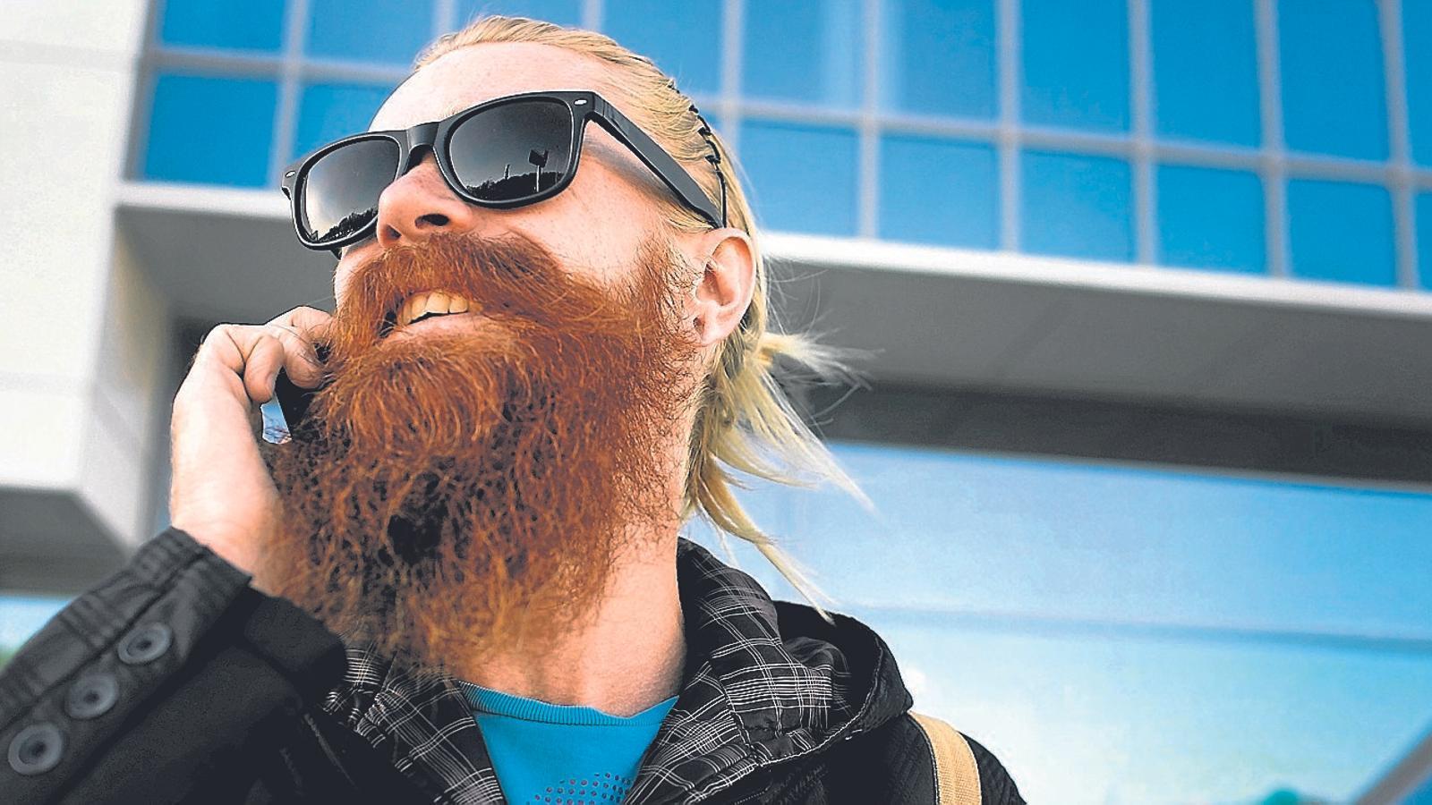 Un jove amb barba parlant pel mòbil