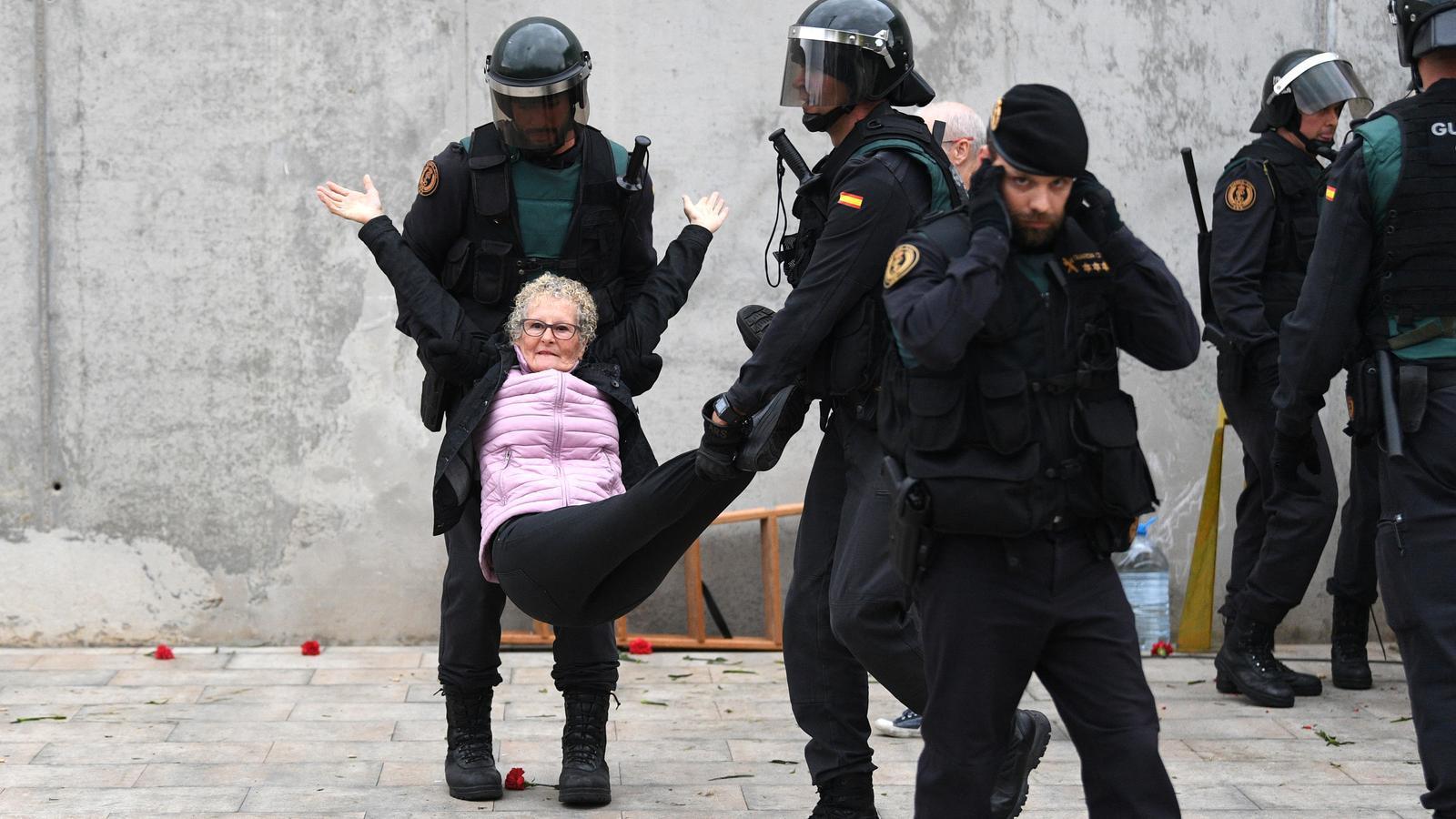 Una dona és retirada per la força per la policia a Sant Julià de Ramis.