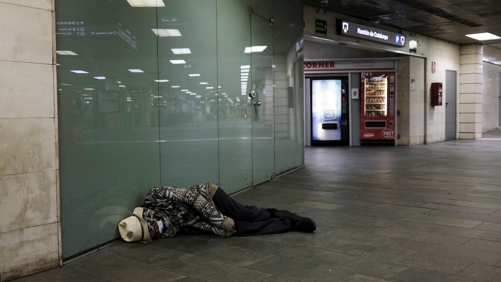 Un home dorm al vestíbul de l'estació de Renfe a la plaça de Catalunya de Barcelona