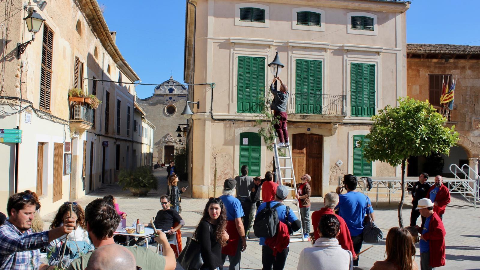 Diversos veïnats penjant brots de pi als carrers del poble per anunciar la festa.