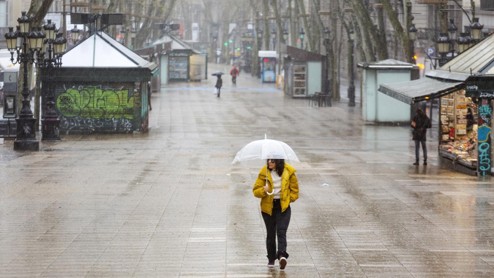 La Rambla de Barcelona gairebé buida durant la crisi del coronavirus en un dia plujós de primavera