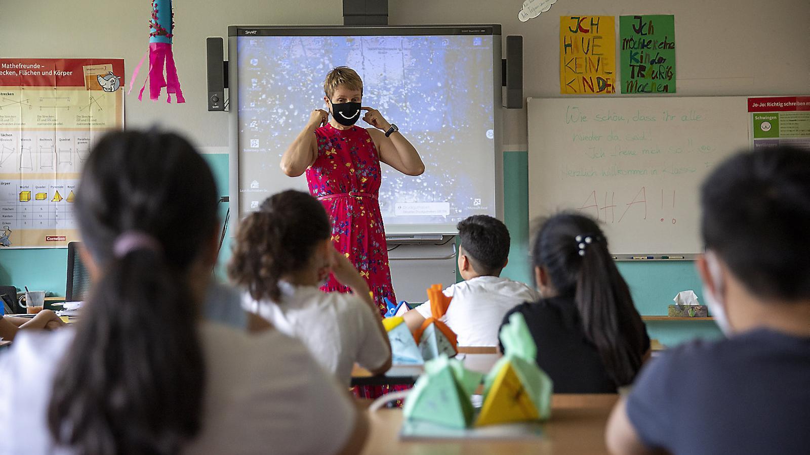 Una professora en una escola de Berlín explicant als alumnes les normes de prevenció contra el  covid-19.