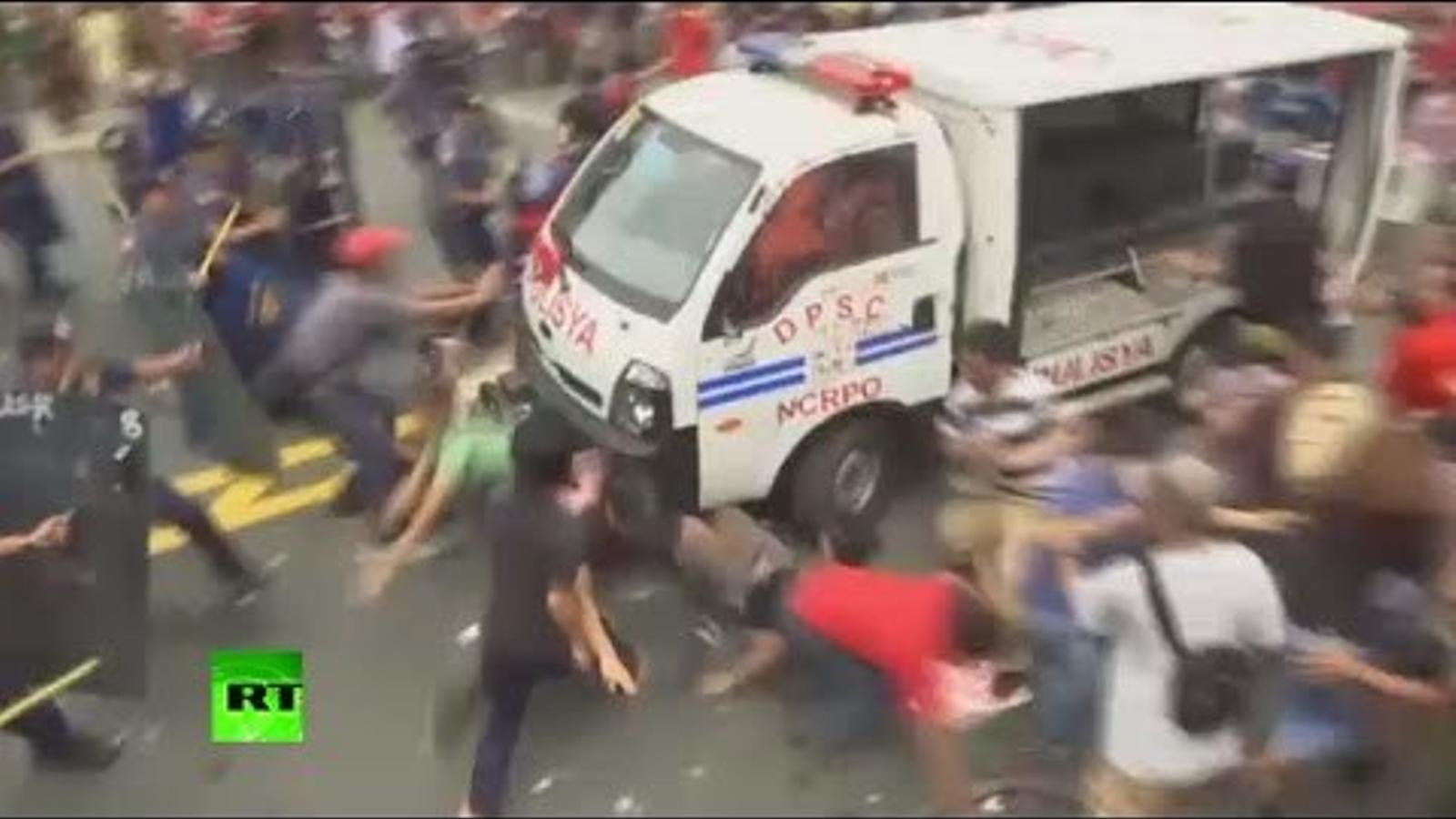 Una furgoneta de la policia filipina envesteix la multitud que es manifestat a l'ambaixada nord-americana de Manila.