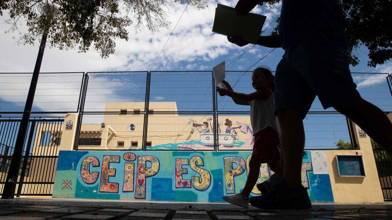 Un home i una nena caminant davant una escola del barri de Son Gotleu, ara confinat.