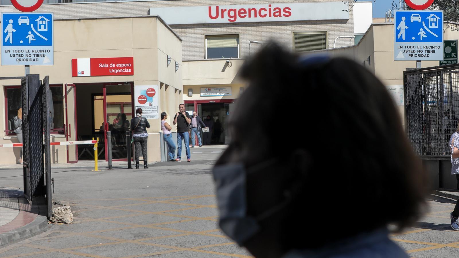 Una dona amb mascareta, davant de la porta d'urgències d'un hospital a Madrid