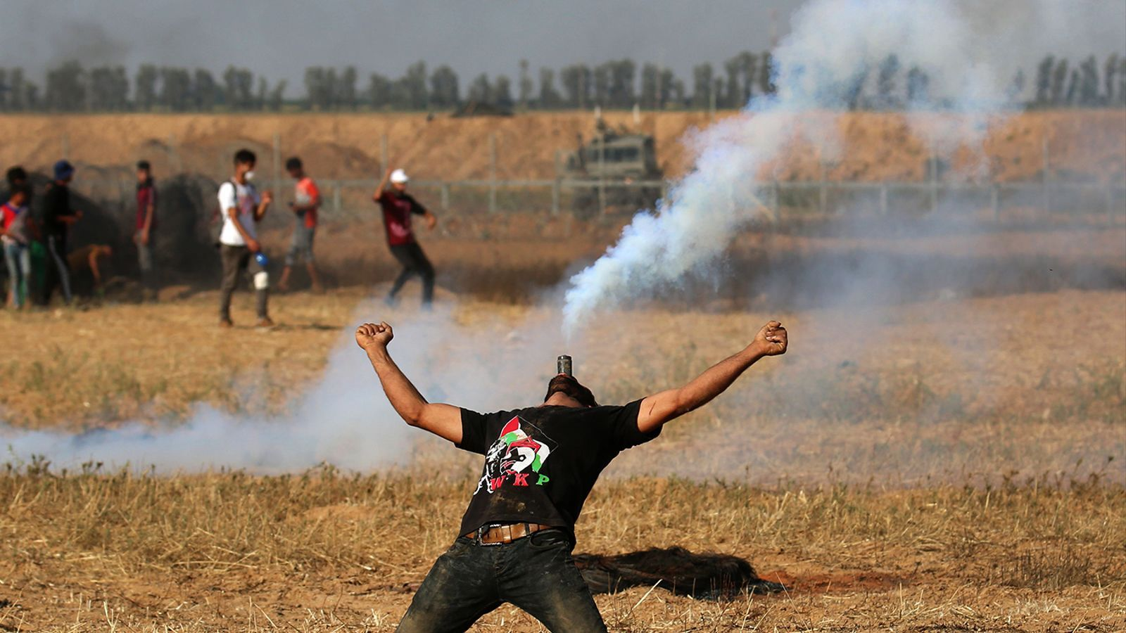 A Palestinian protestor carrying a tear gas cartridge in his mouth during a demonstration along the Israeli border east of Khan Yunis in the southern part of Gaza