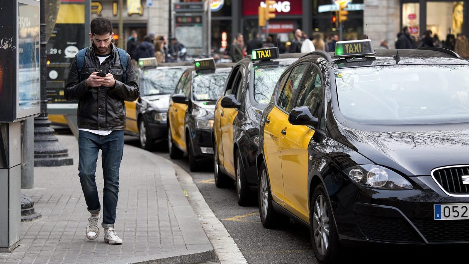Un vianant caminant al costat de la parada de taxis de la plaça Catalunya, a Barcelona.