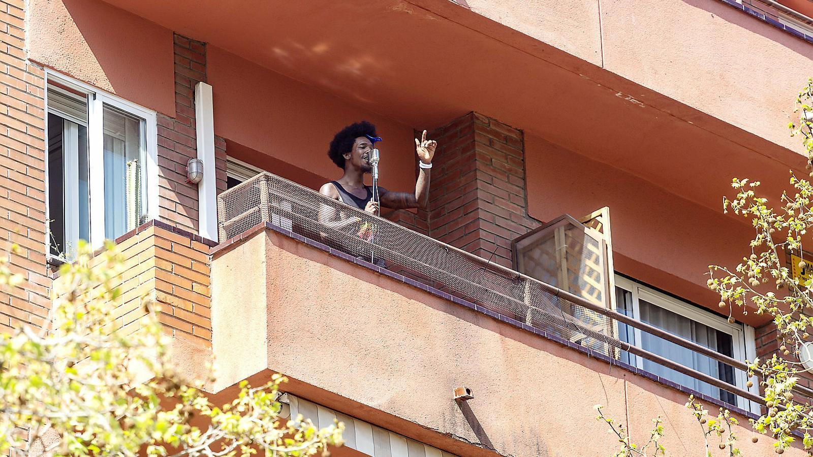 Un veí canta des d'un balcó a l'avinguda Gaudí durant el confinament.