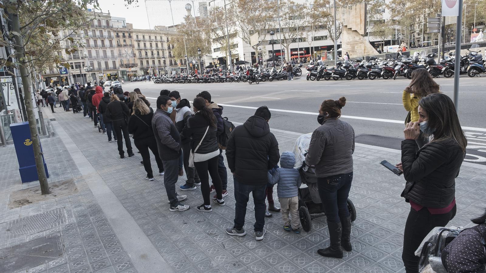 Desenes de persones fan cua per entrar en una botiga a la plaça de Catalunya, a Barcelona