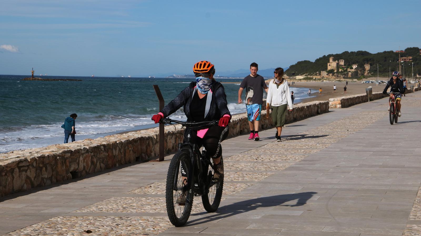 Ciclistes i persones caminant pel passeig marítim d'Altafulla en el primer dia permès per sortir a passejar i practicar esport, el 2 de maig