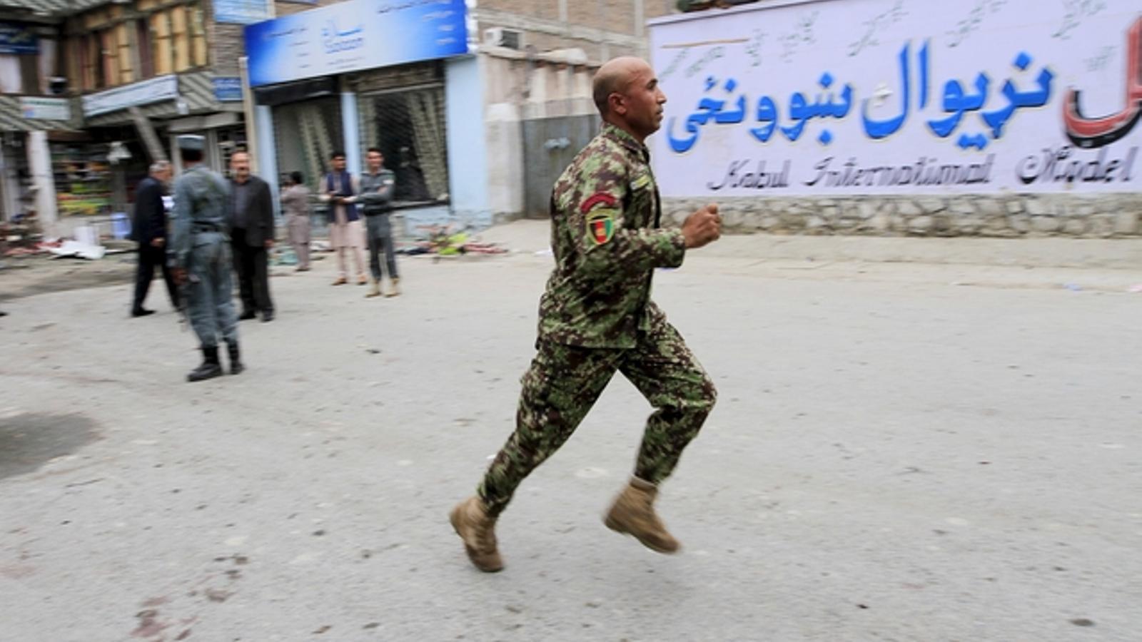 Un agent de les forces de seguretat corre en el lloc de l'atemptat. REUTERS