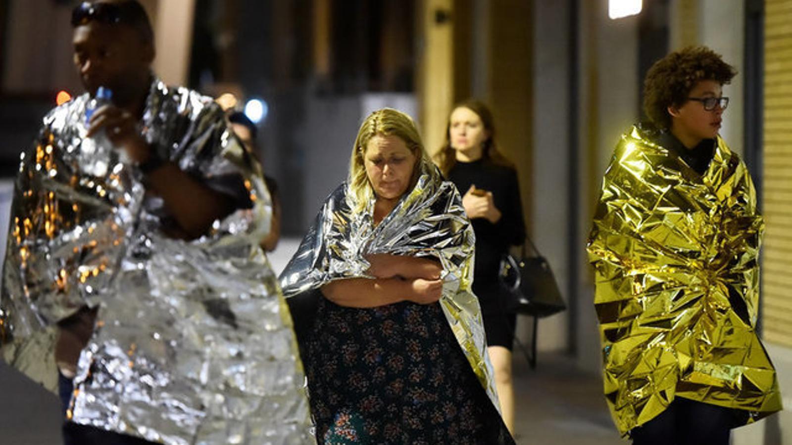 Tres joves abandonen la zona afectada coberts amb mantes tèrmiques. / HANNAH MCKAY / REUTERS