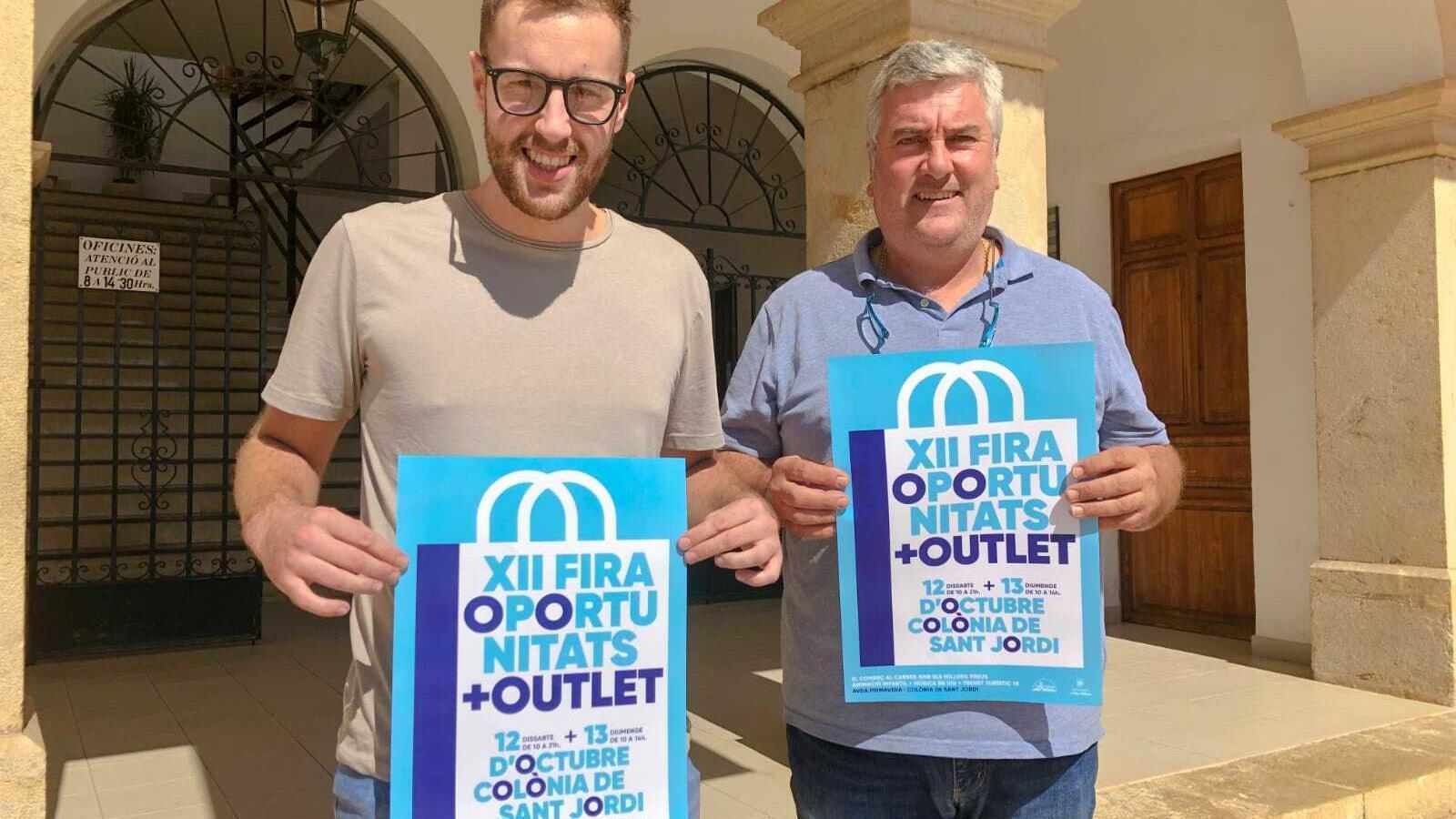 Miquel A. Garí, portaveu de la Junt de Districte i Miquel Rigo, regidor de Comerç, amb el cartell promocional.