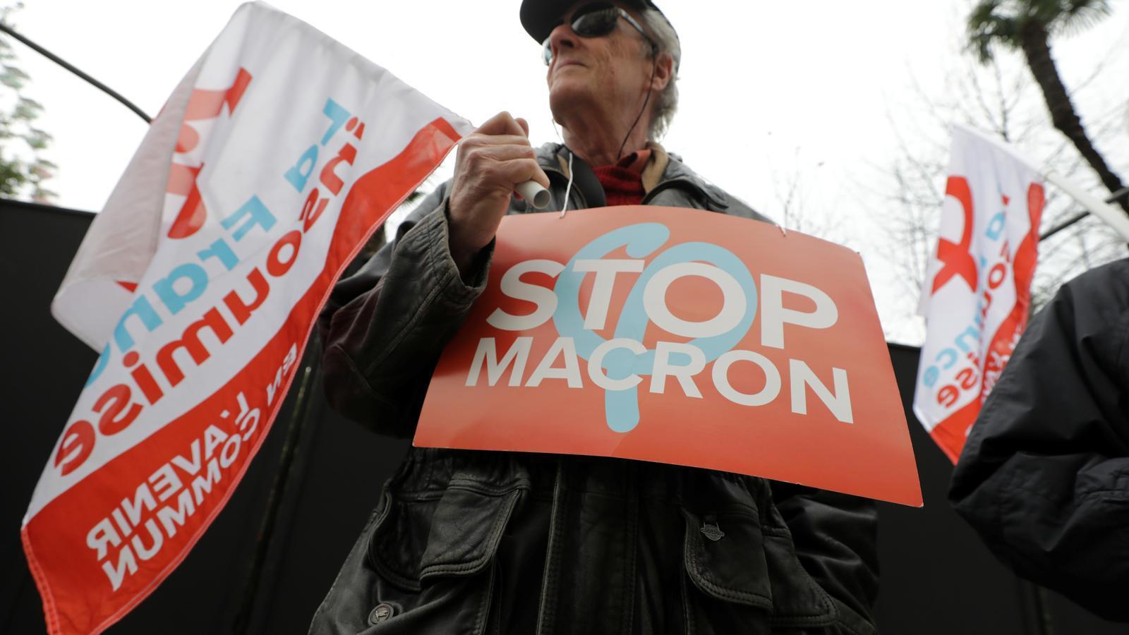 Un manifestant amb una pancarta que demana frenar Macron durant la vaga contra les pensions, a París