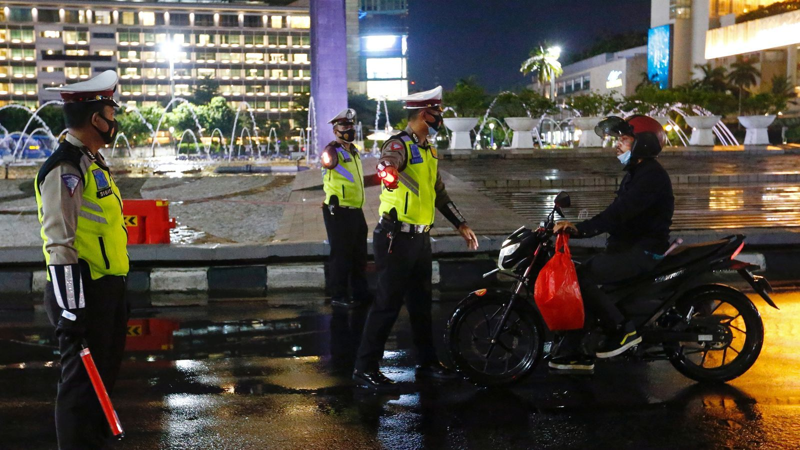 Agents de la policia aturen un ciutadà que viatja en motocicleta a Jakarta.