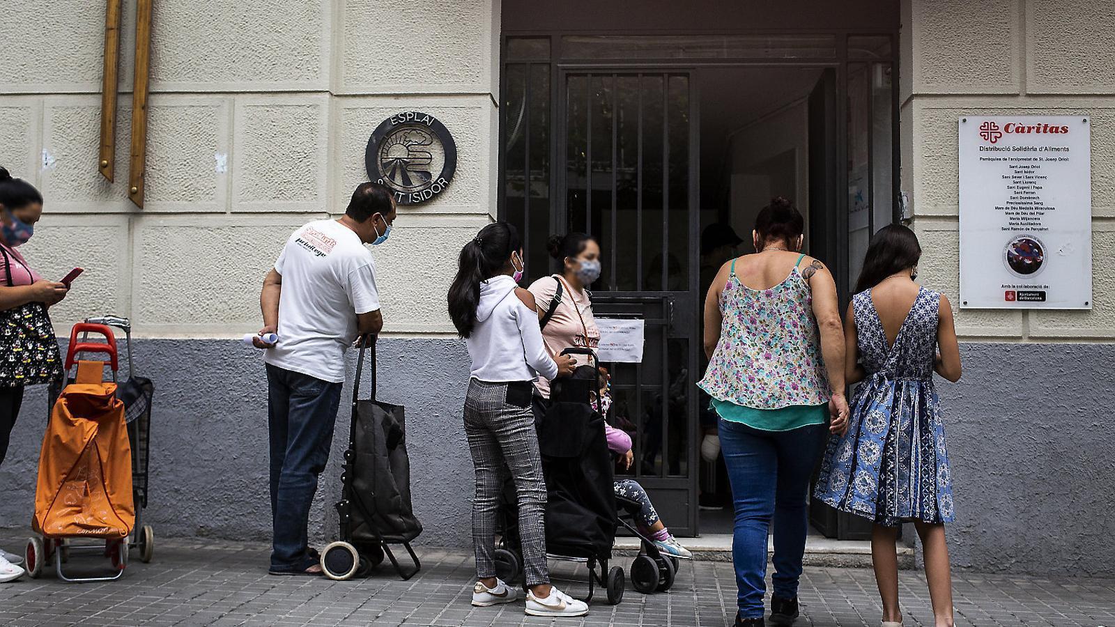 Cua de persones a l'Eixample de Barcelona esperant per rebre els aliments que distribueix Càritas.