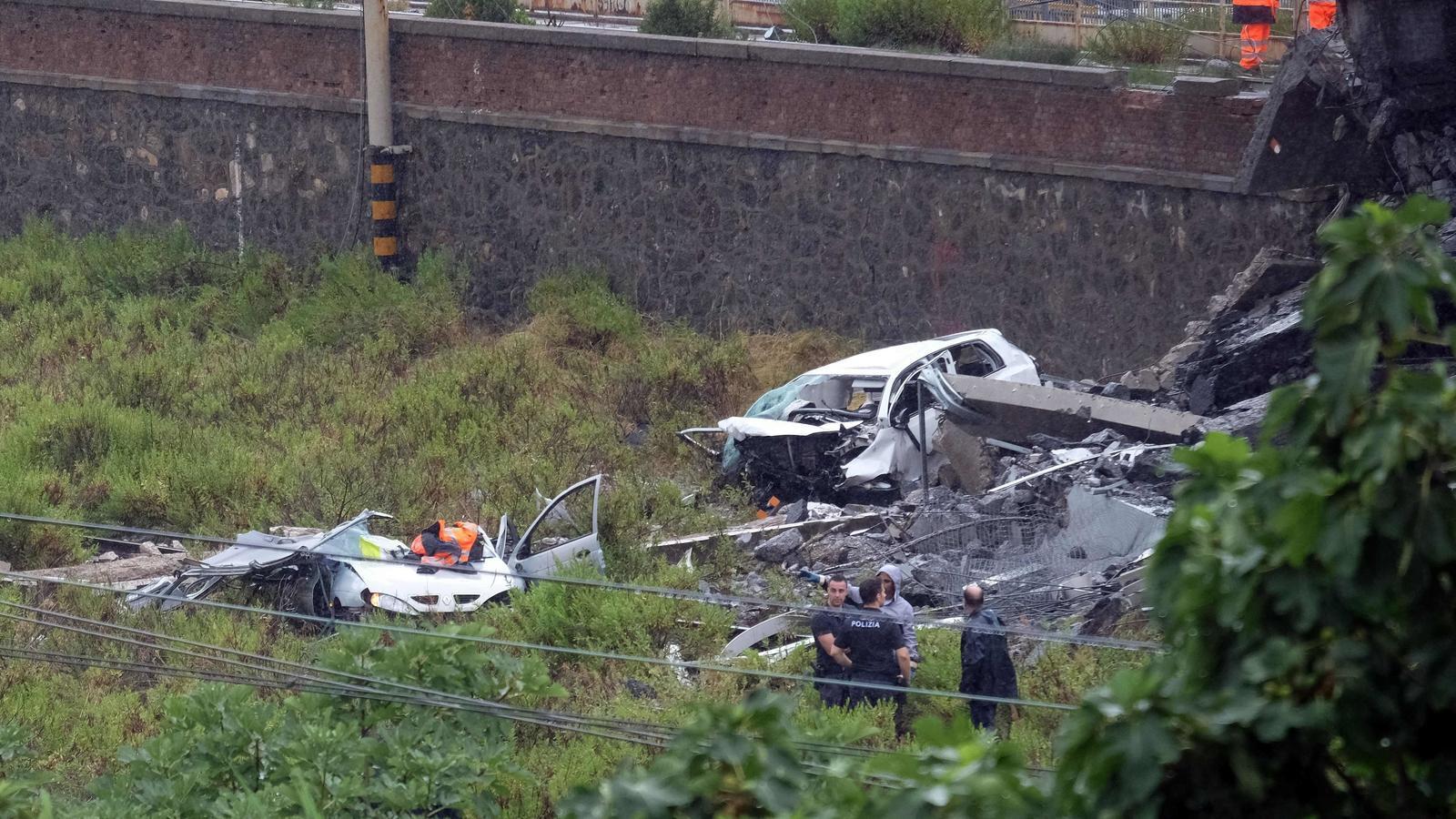 El serveis de rescat busquen supervivent entre els cotxes qua han caigut al buit amb l'esfondrament del pont Morandi
