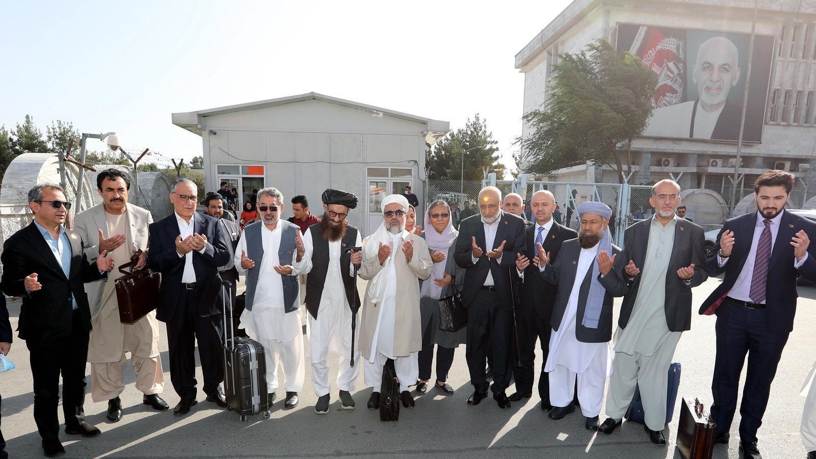 Part de l'equip negociador del govern afganès resa a l'aeroport de Kabul abans d'emprendre el viatge a Doha