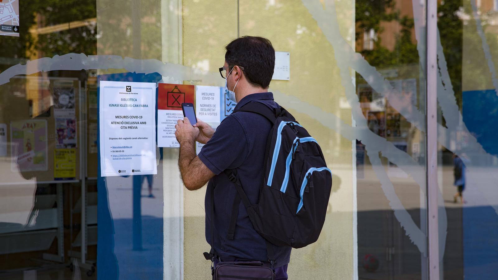 Un usuari a l'entrada de la biblioteca Ignasi Iglésias-Can Fabra