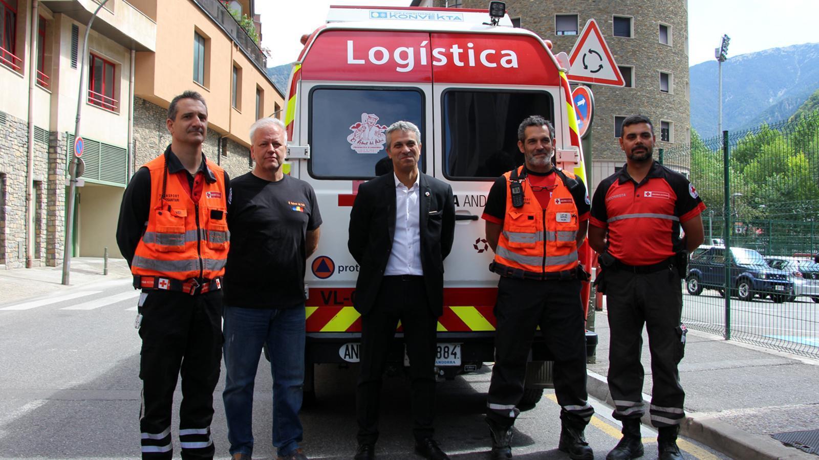 El representant del Rebost del Padrí, Josep Maria Escolà, i el director de la Creu Roja Andorrana, Jordi Fernández, junt amb altres membres de l'entitat al davant del camió refrigerat on es transporta el menjar. / T. N. (ANA)