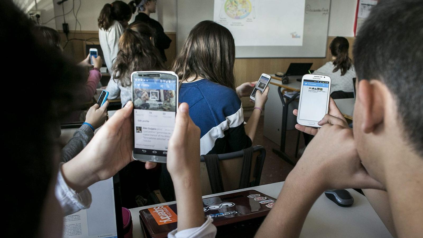 Alumnes utilitzant el Twitter durant una classe de robòtica. A partir del curs vinent tots els centres educatius hauran de regular l'ús dels smartphones.