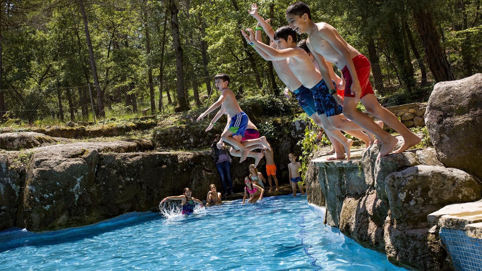 Un grup de nens banyant-se durant el primer dia de casals d'estiu de Fundesplai, a Sau.