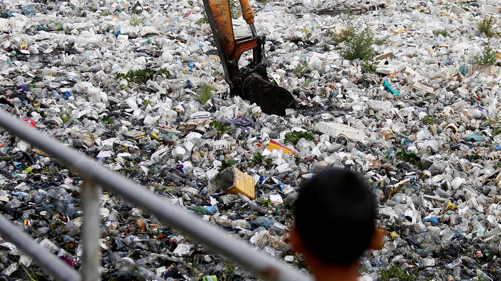 Recullida d'ampolles de plàstic i altres residus en un canal de clavegueram a Phnom Penh, Cambodja
